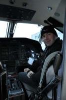 Ken Wright in the business end of the PC-12.: Ken, wearing his OFC gear, at the First Officer position of the PC-12.